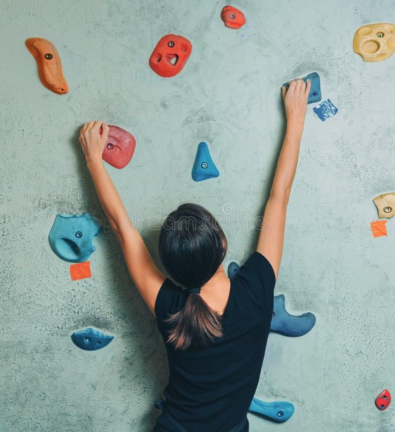 Den sportiga kvinnan som klättrar upp på, vaggar väggen inomhus arkivfoton
