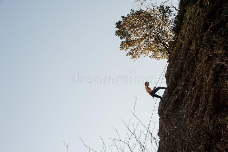 Den sportiga kvinnan som utrustas med ett rep som abseiling på slutta, vaggar arkivfoton