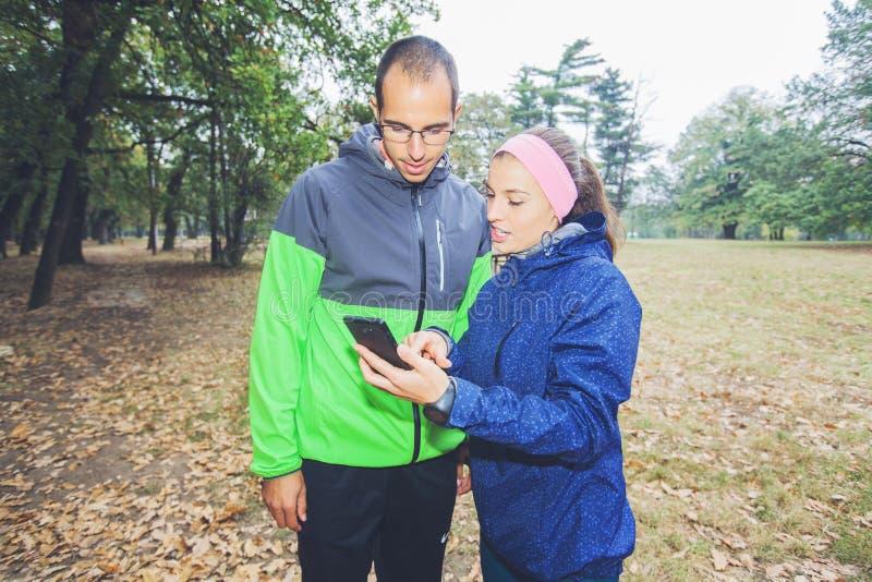 Den sportiga mannen och kvinnor förbereder sig för utomhus- genomkörare arkivbilder