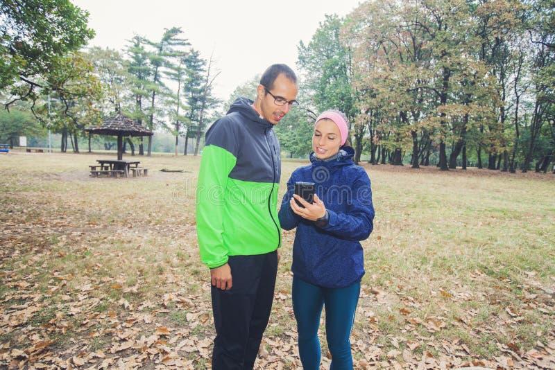 Den sportiga mannen och kvinnor förbereder sig för utomhus- genomkörare royaltyfri fotografi