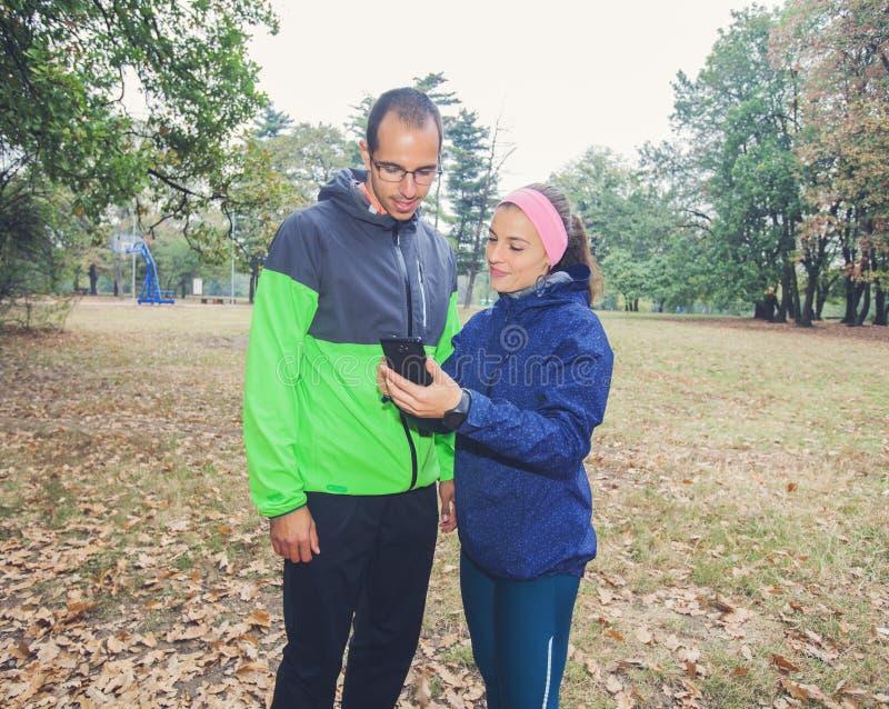 Den sportiga mannen och kvinnor förbereder sig för utomhus- genomkörare royaltyfri bild