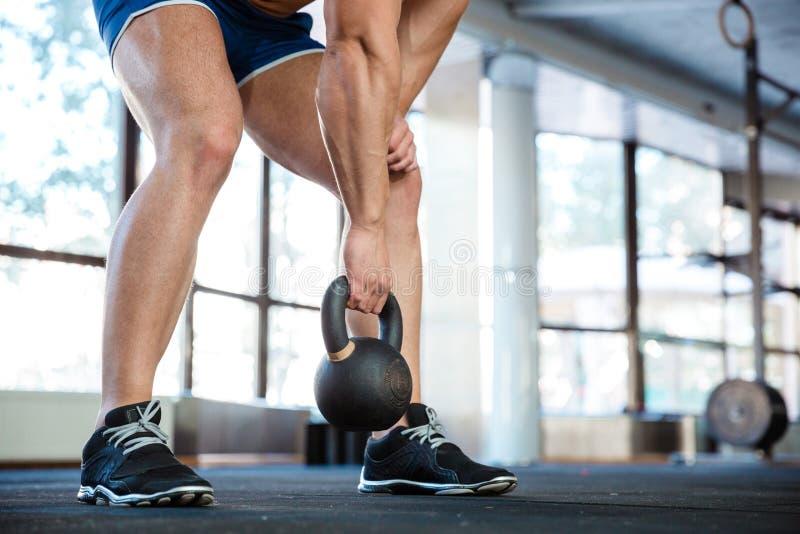 Den sportiga mannen räcker och lägger benen på ryggen lyftande kokkärlbollen royaltyfria foton
