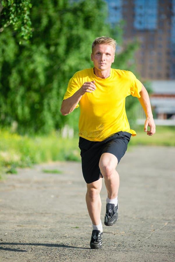 Den sportiga mannen som joggar i stadsgata, parkerar Utomhus- kondition royaltyfria foton