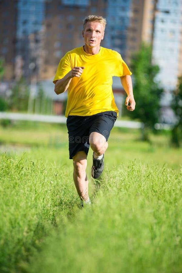 Den sportiga mannen som joggar i stadsgata, parkerar Utomhus- kondition arkivfoto