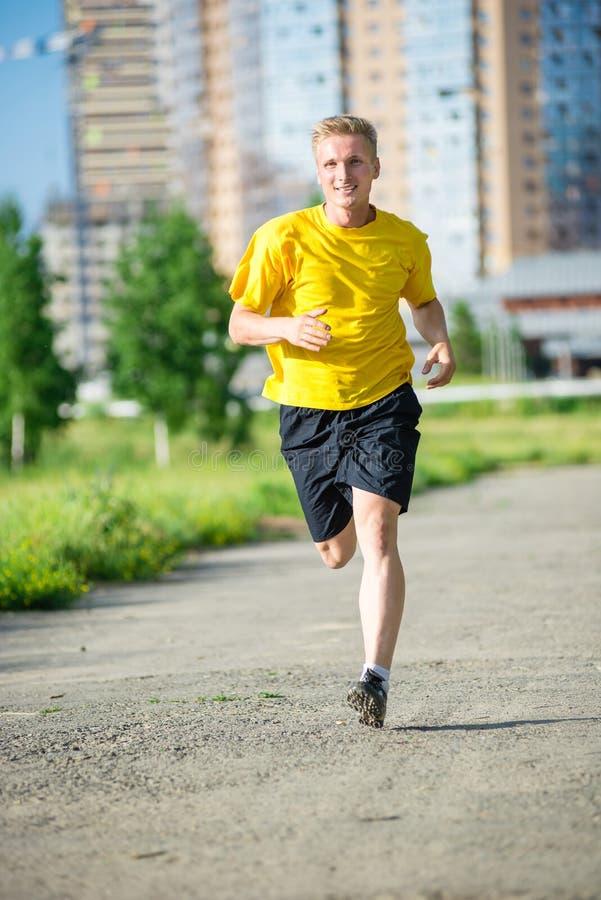 Den sportiga mannen som joggar i stadsgata, parkerar Utomhus- kondition arkivbild