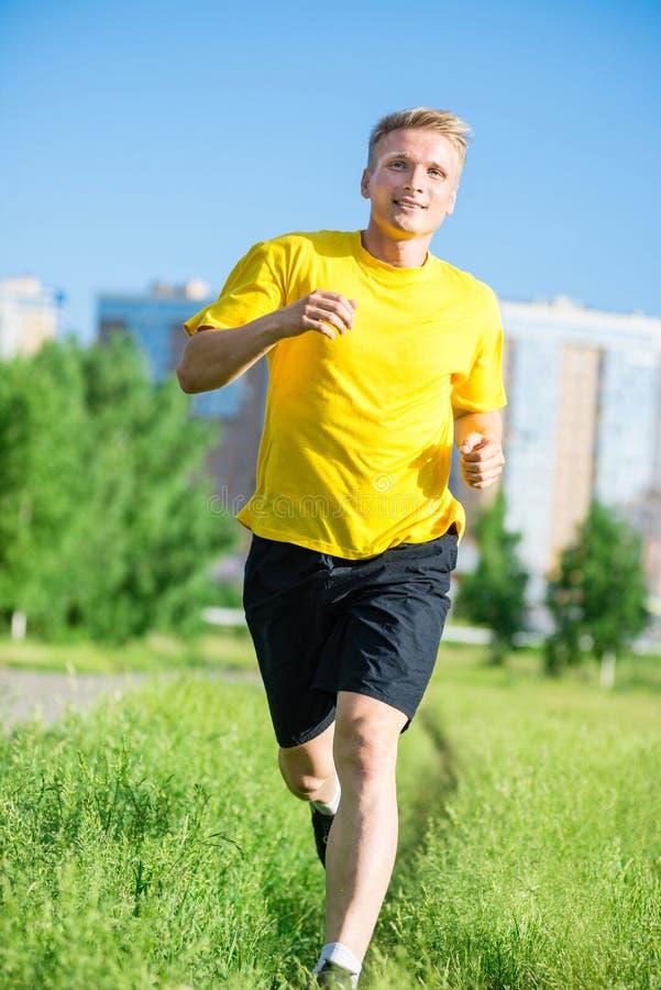 Den sportiga mannen som joggar i stadsgata, parkerar Utomhus- kondition arkivbilder