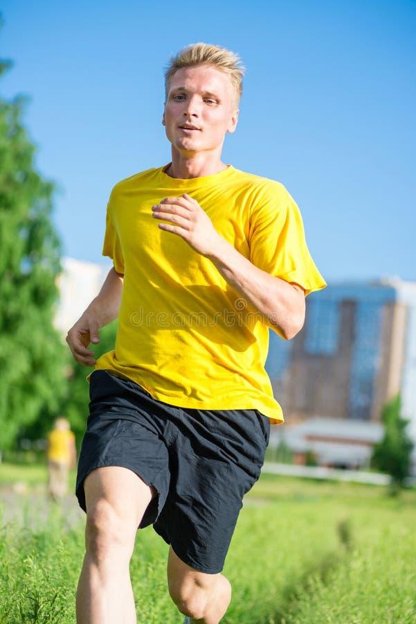 Den sportiga mannen som joggar i stadsgata, parkerar Utomhus- kondition royaltyfri bild