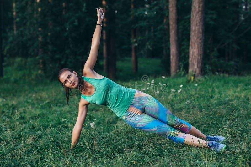 Den sportiga slanka idrottskvinnan som gör sidoplankayoga, poserar anseende på gräs i sommarmorgon arkivfoton