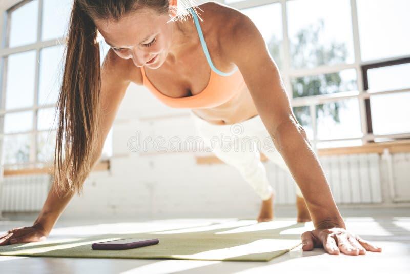 Den sportiga starka kvinnan som gör push-UPS på matt kondition och blickar på smartphonen för räkningar, resulterar royaltyfria foton