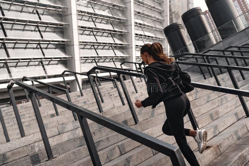 Den sportiga unga kvinnan kör uppför trappan utomhus isolated rear view white royaltyfri foto