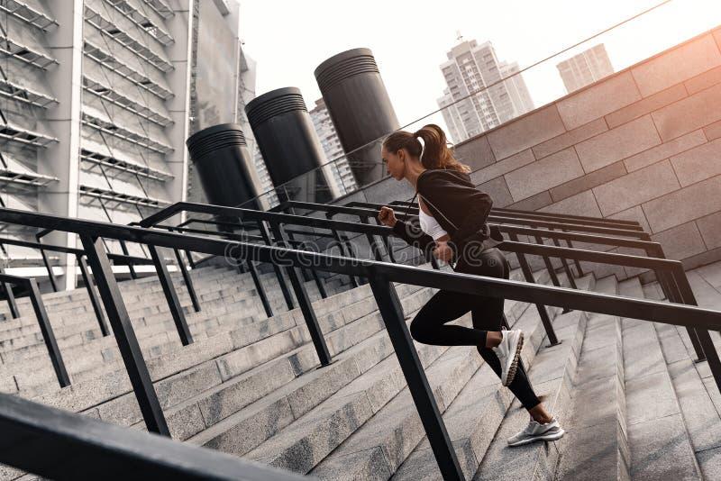Den sportiga unga kvinnan kör uppför trappan utomhus Slapp fokus royaltyfria bilder