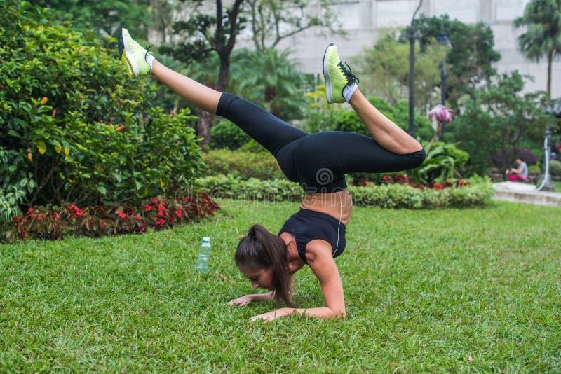 Den sportiga unga kvinnan som gör handstansövning med att böja, lägger benen på ryggen på gräs parkerar in Praktiserande yoga för royaltyfri fotografi
