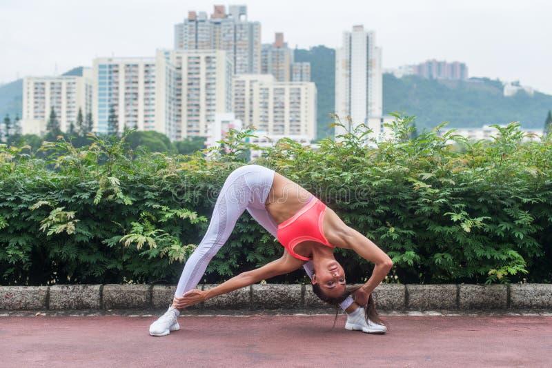 Den sportiga unga kvinnan som sträcker göra yogatriangeln, poserar anseende i denlade benen på ryggen positionen som böjer för at arkivbild