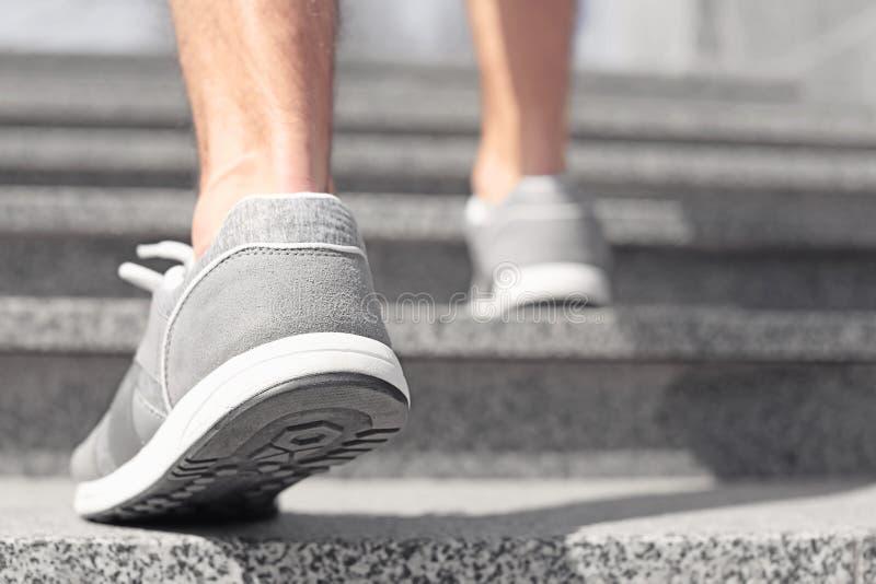 Den sportiga unga mannen i utbildning skor utomhus royaltyfri fotografi