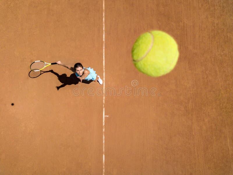 Den Sportive flickan spelar tennis royaltyfri bild