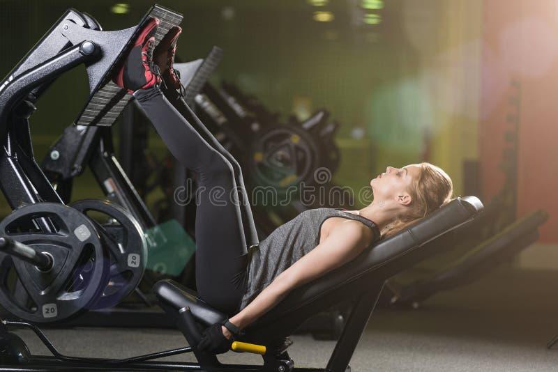 Den Sportive kvinnan som använder vikter, trycker på maskinen för ben idrottshall royaltyfri bild