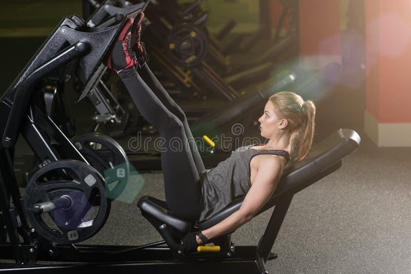 Den Sportive kvinnan som använder vikter, trycker på maskinen för ben idrottshall arkivbild
