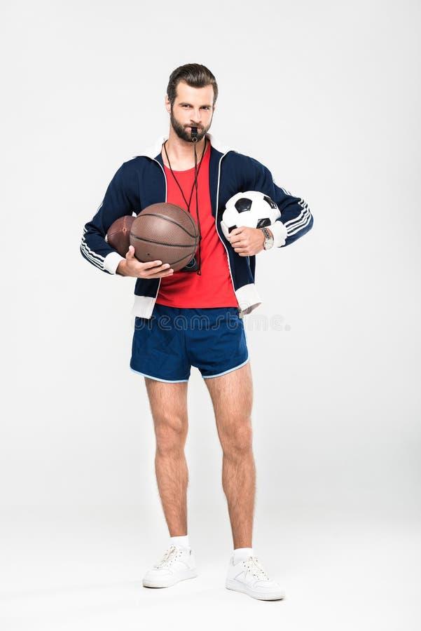 den sportive lagledaren med rugby, basket och fotboll för vissling hållande klumpa ihop sig, royaltyfri bild