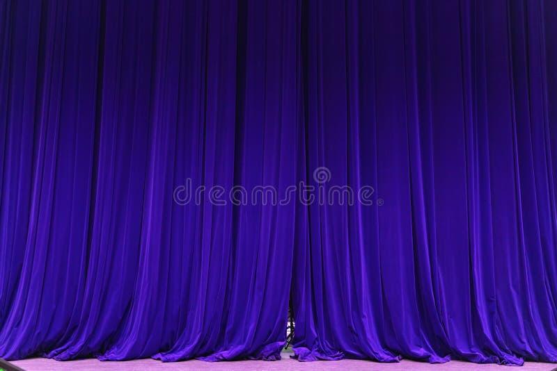 Den stängda blåa strålen för gardinbakgrundsstrålkastaren exponerade draperar scenisk royaltyfria bilder