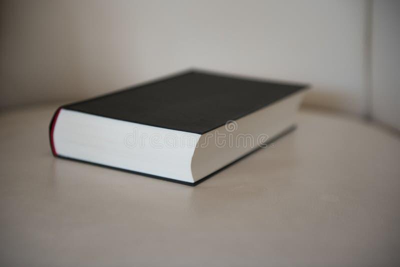Den stängda boken ligger på en läderstol arkivfoto