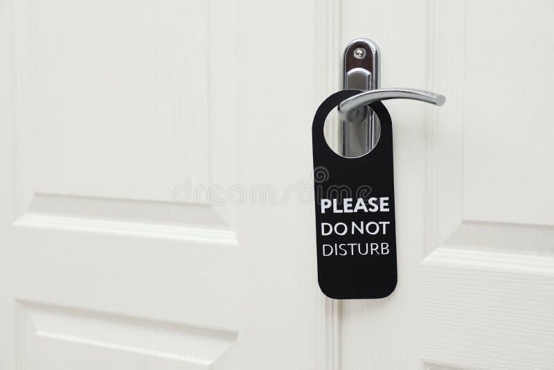 Den stängda dörren med tecknet PLEASE STÖRER INTE på handtaget på hotellet royaltyfria bilder