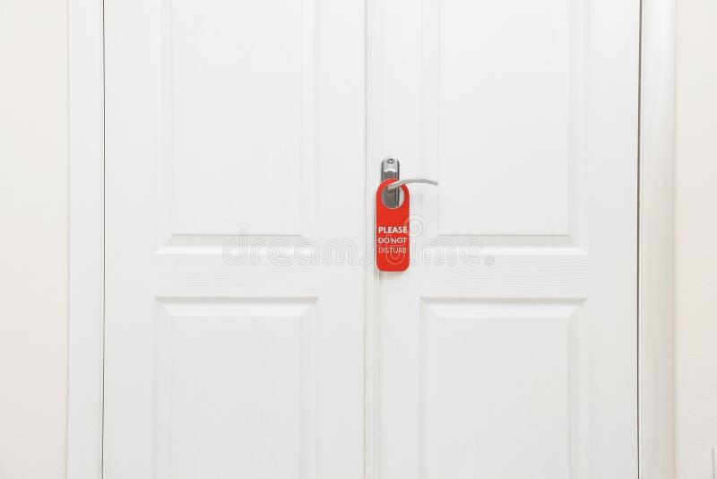 Den stängda dörren med tecknet PLEASE STÖRER INTE på handtaget arkivfoto