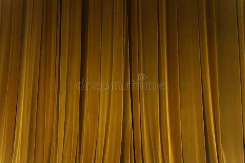 Den stängda gula strålen för gardinbakgrundsstrålkastaren exponerade draperar scenisk royaltyfri fotografi