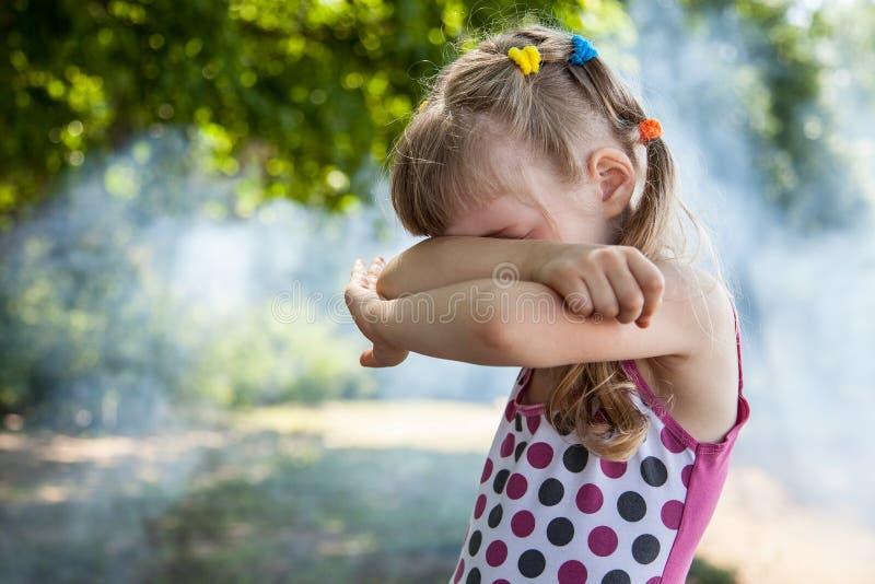 Den stängda lilla flickan synar henne armar royaltyfri foto