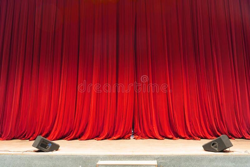 Den stängda röda strålen för gardinbakgrundsstrålkastaren exponerade draperar scenisk arkivfoto