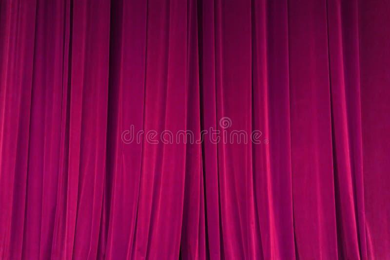 Den stängda röda strålen för gardinbakgrundsstrålkastaren exponerade draperar scenisk royaltyfri foto