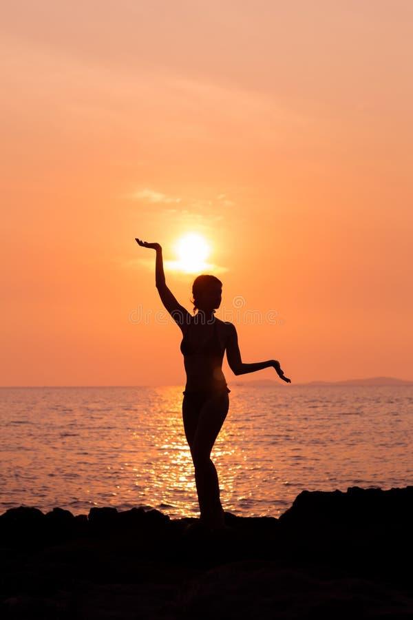 Den stående kvinnakonturn i yoga poserar på tänd havsbakgrundsbaksida royaltyfri bild