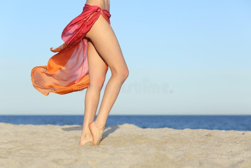 Den stående kvinnan lägger benen på ryggen att posera på stranden som bär en pareo royaltyfri fotografi