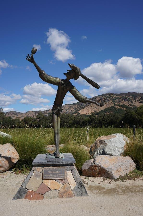 Den större skulpturen av fullvuxen hankronhjort`en hoppar framme vinodlingen i Napa Valley, Kalifornien arkivfoto
