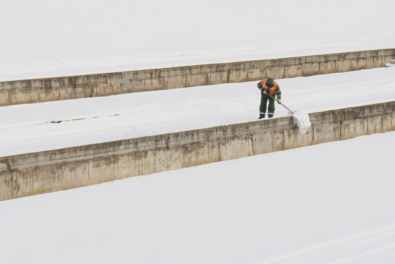 Den stads- arbetaren gör klar snö Snöborttagning efter tungt snöfall, stadsservice för förbättringen av staden Kommunal arbetare  arkivbild