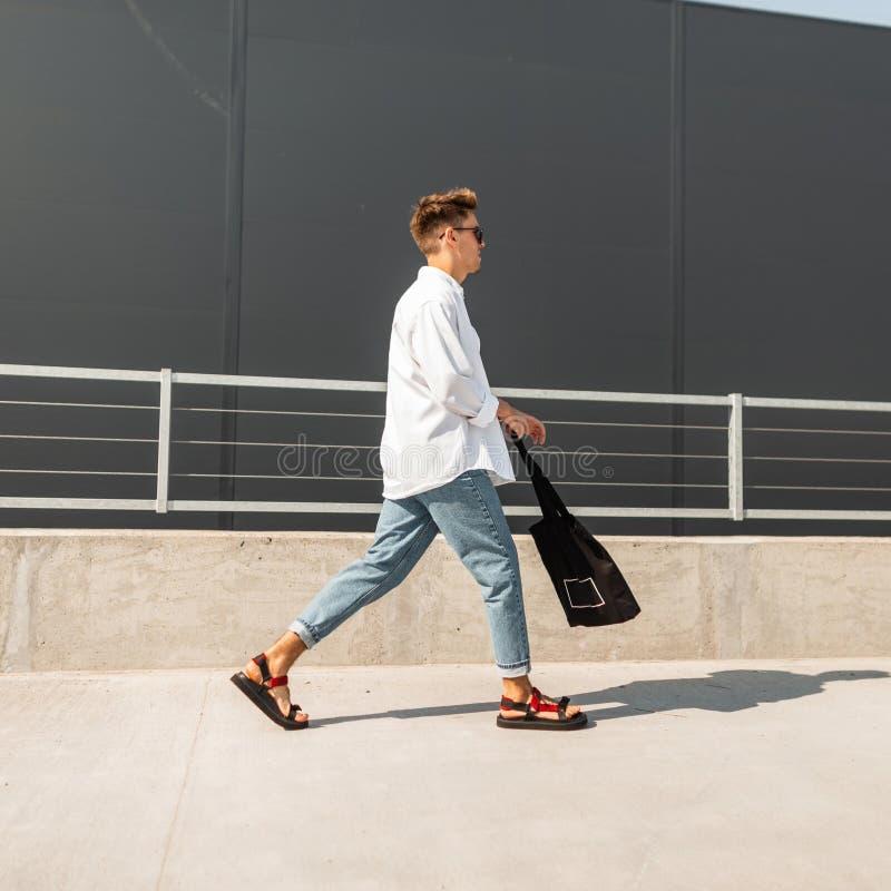 Den stads- för hipstermode för den unga mannen modellen i tappningjeans i en stilfull skjorta i trendiga sandaler i solglasögon m arkivbild