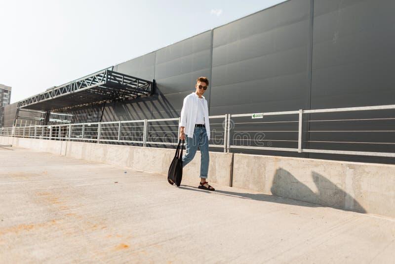 Den stads- hipsteren för den unga mannen i stilfull vita och grov bomullstvillkläder i moderiktiga sandaler med en svart torkduke arkivfoto