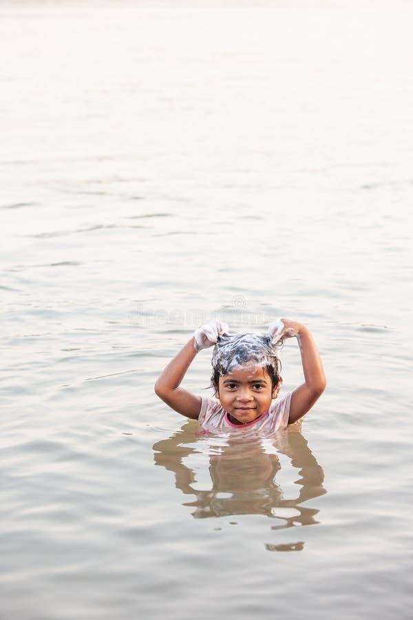Den stamBru lilla flickan är le och genom att använda schampo, medan ta duschen i Mekonget River i varmt väder för sommar Bru by, royaltyfri fotografi