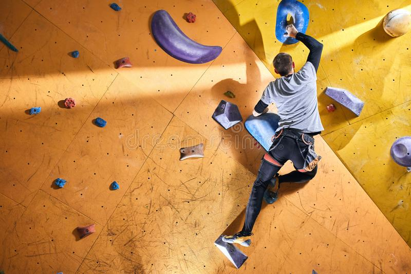 Den starka aktiva mannen med fysiskt handikapp tycker om bouldering hobby arkivbild