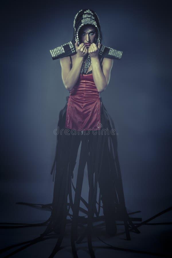 Den starka dansen, den härliga brunettkvinnan i harnesk bildade vid spegeln royaltyfri bild