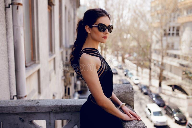 Den starka eleganta kvinnan i svart solglasögon, den sexiga svarta klänningen, hårhästsvans, ser med inställning på balkongen royaltyfria bilder