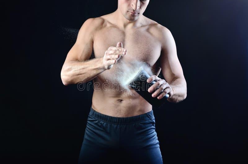Den starka idrotts- mannen häller proteinnäringtillägget in i en svart plast- shaker royaltyfri bild
