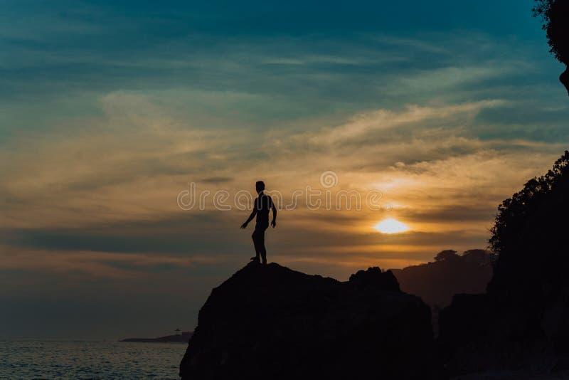 Den starka konditionyogamannen på vaggar stranden nära havet Harmoniskt begrepp, fred och framgång silhouette arkivfoto