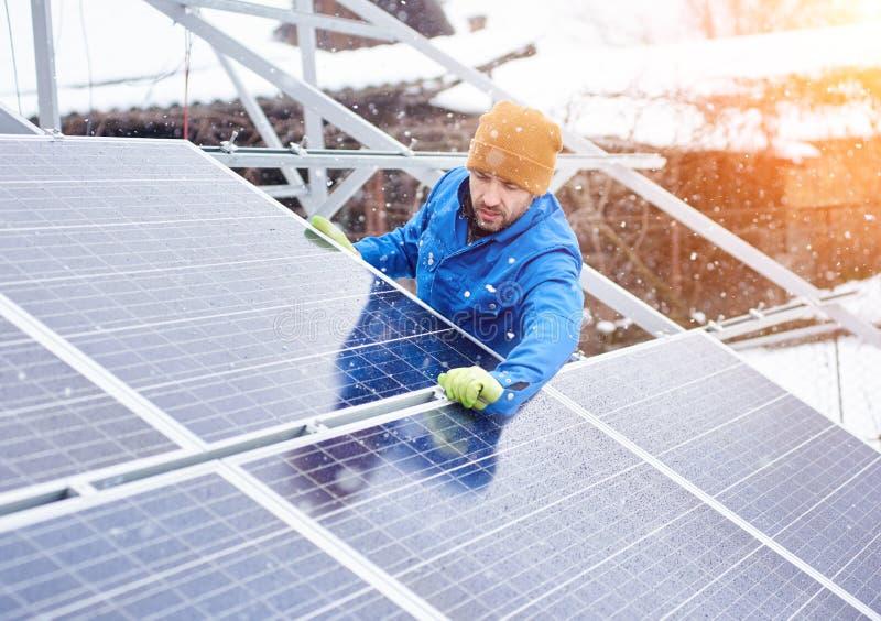 Den starka manliga teknikeren i blått passar installera photovoltaic blåa sol- enheter som förnybara energikällorkälla arkivbild