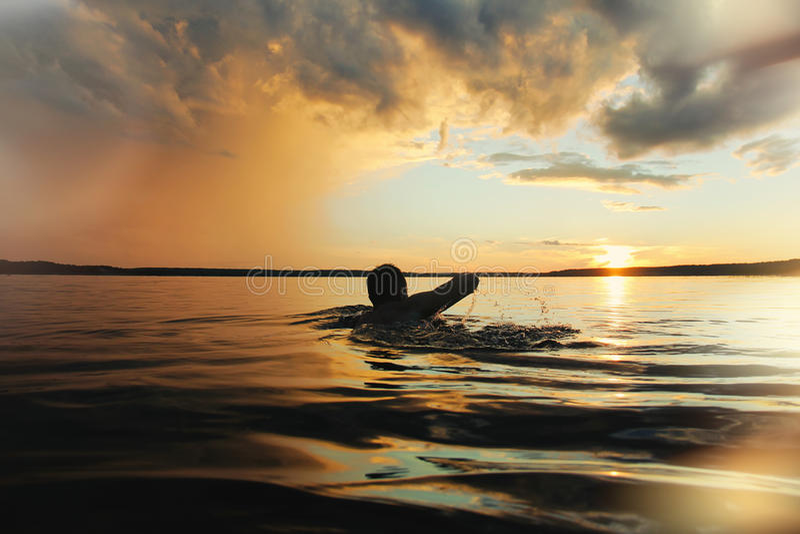 Den starka mannen seglar in i solnedgången Lens signalljuseffekt royaltyfria foton