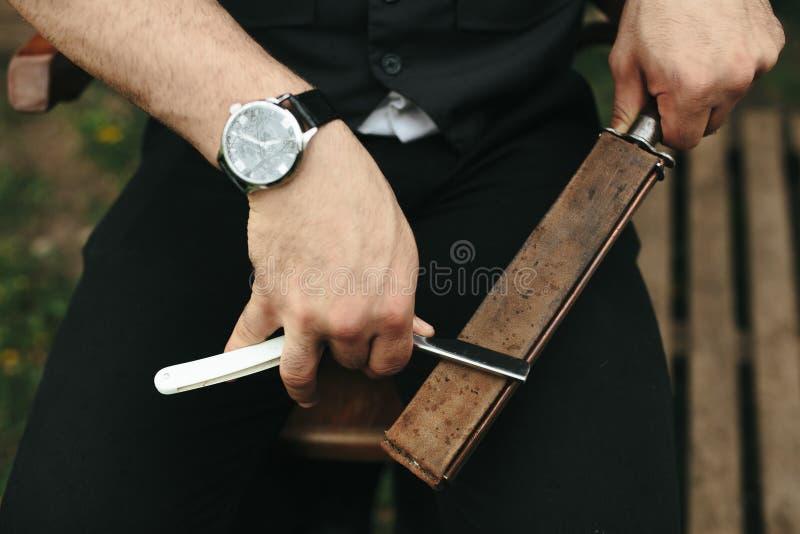 Den starka mannen vässar den gamla rakkniven arkivfoto