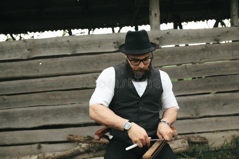 Den starka mannen vässar den gamla rakkniven arkivbilder