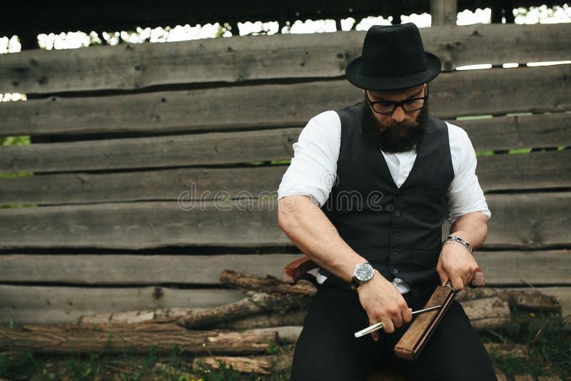 Den starka mannen vässar den gamla rakkniven arkivfoton