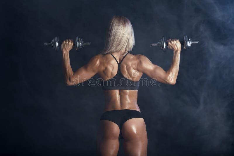 Den starka sexiga kvinnan utbildar med skivstånger arkivbild