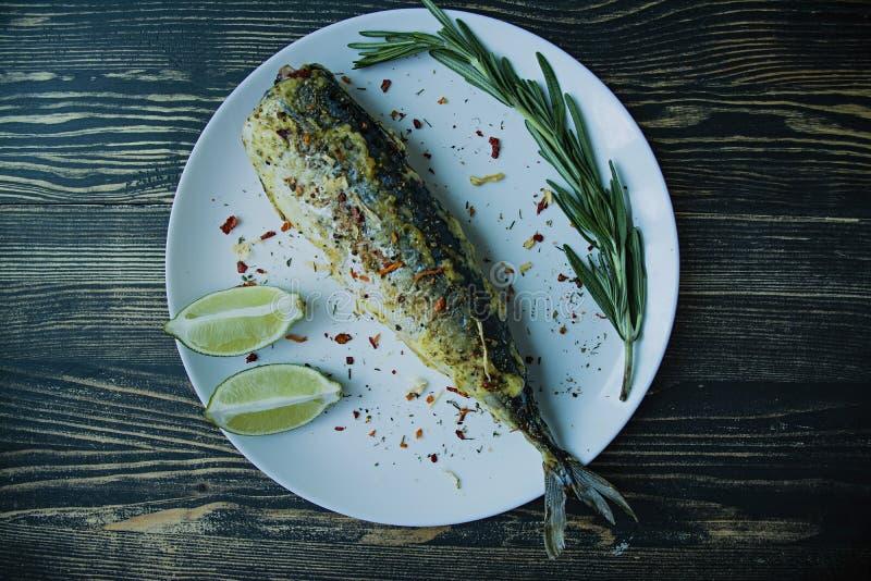 Den stekte makrillen tj?nade som p? en platta som dekorerades med kryddor, ?rter och gr?nsaker Riktig n?ring ovanf?r sikt m?rkt t royaltyfri bild