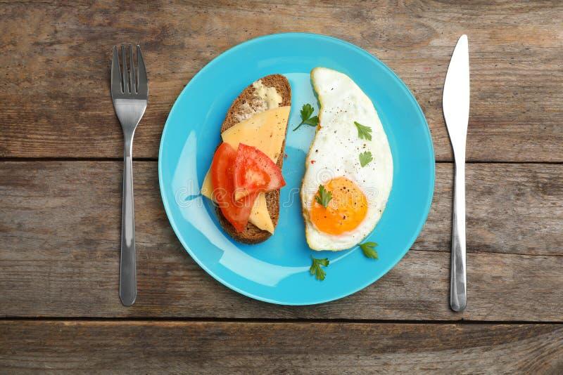 Den stekte soliga sidan upp ägget och smörgåsen tjänade som på trätabellen royaltyfria bilder